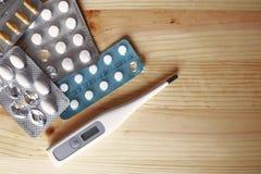 Pillole della compressa in blister e termometro bianco Fotografie Stock Libere da Diritti