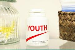 Pillole della gioventù in una bottiglia sulla mensola della stanza da bagno fotografia stock libera da diritti