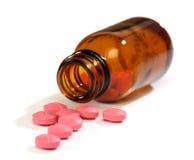 Pillole della medicina che straripano una bottiglia Fotografia Stock