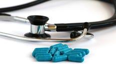 Pillole della medicina e dello stetoscopio su un fondo bianco Tecnologia della medicina e concetto di sanità fotografia stock libera da diritti