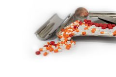 Pillole delle capsule e vassoio arancio della droga su fondo bianco con il poliziotto fotografia stock libera da diritti