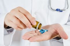 Pillole di versamento di medico sulla sua mano Concetto medico in ospedale Immagini Stock Libere da Diritti