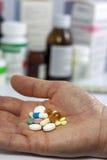 Pillole a disposizione contro le medicine in farmacia Immagine Stock Libera da Diritti