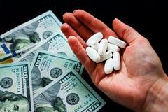 Pillole a disposizione e dolary bianchi su un fondo nero Molte pillole psichedeliche fotografia stock libera da diritti