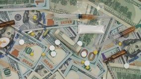 Pillole, droghe, cocaina, siringa sulle banconote del dollaro Rotazione del biglietto stock footage