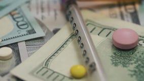 Pillole, droghe, cocaina, siringa sulle banconote del dollaro Tiro del carrello video d archivio