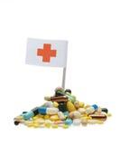 Pillole e bandiera della croce rossa Immagini Stock Libere da Diritti