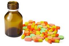Pillole e bottiglia della compressa isolata nel bianco Fotografia Stock