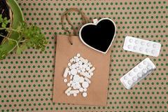pillole e capsule bianche, sacchetto della spesa fatto a mano, borsa del regalo e bl fotografie stock