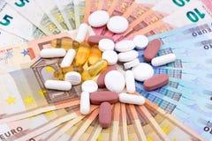Pillole e capsule su soldi Immagini Stock