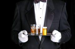 Pillole e cocktail della holding dell'uomo sul cassetto d'argento Fotografie Stock Libere da Diritti