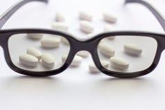Pillole e compresse bianche con i vetri su fondo leggero Farmacia e medicina per il concetto degli occhi immagini stock
