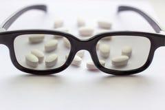 Pillole e compresse bianche con i vetri su fondo leggero Farmacia e medicina per il concetto degli occhi immagine stock libera da diritti
