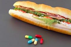 Pillole e due hot dog con i vari ingredienti Fotografie Stock