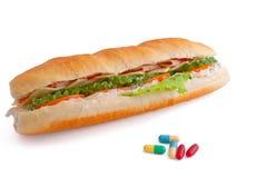 Pillole e due hot dog con i vari ingredienti Immagini Stock Libere da Diritti
