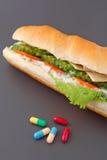 Pillole e due hot dog con i vari ingredienti Fotografia Stock