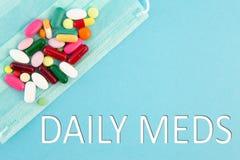 Pillole e maschera chirurgica con il testo quotidiano dei meds fotografia stock libera da diritti