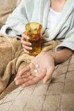 Pillole e vetro della holding della donna. Fotografia Stock Libera da Diritti