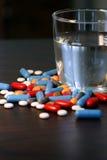 Pillole e vetro di acqua Immagini Stock