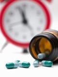 Pillole ed orologio Fotografia Stock