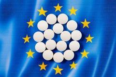 Pillole farmaceutiche rotonde bianche sul fondo della bandiera di Unione Europea Immagine Stock