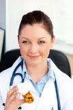 Pillole femminili sorridenti della holding del medico nel suo ufficio Immagine Stock