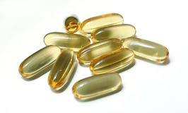 Pillole gialle del gel su un fondo bianco Immagine Stock