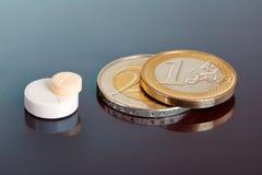 Pillole impilate vicino agli accoppiamenti delle monete euro Fotografia Stock