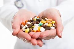 Pillole in mani del medico Immagine Stock