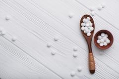 pillole mediche bianche sul cucchiaio di legno Fotografie Stock