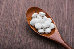 pillole mediche bianche sul cucchiaio di legno Immagini Stock Libere da Diritti