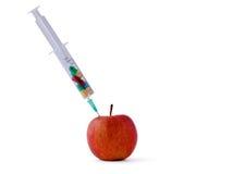Pillole mediche del witn della siringa e mela rossa che si trovano lo scrittorio, isolato su fondo bianco Immagini Stock Libere da Diritti