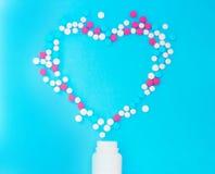 Pillole multicolori dai barattoli bianchi su un fondo blu fotografia stock libera da diritti