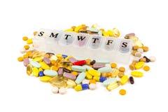 Pillole multicolori nella zona di un pianificatore quotidiano della pillola fotografia stock libera da diritti