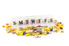 Pillole multicolori nella zona di un pianificatore quotidiano della pillola immagini stock libere da diritti