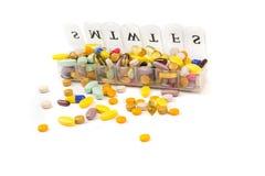 Pillole multicolori nella zona di un pianificatore quotidiano della pillola fotografia stock