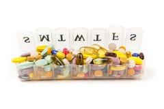 Pillole multicolori nella zona di un pianificatore quotidiano della pillola immagini stock