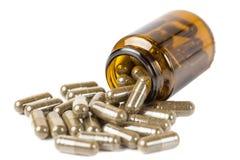 Pillole o compresse dell'isolato nella bottiglia marrone di vetro su un fondo bianco fotografia stock