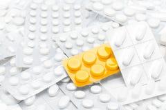 Pillole in pacchetto giallo sopra i ridurre in pani bianchi Fotografie Stock Libere da Diritti