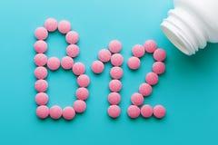 Pillole rosa sotto forma della lettera B12 su un fondo blu, rovesciato da una latta bianca fotografia stock