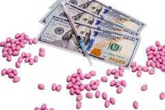 Pillole rosa sparse su un fondo bianco accanto a $300 fatture di dollaro americano e ad una siringa Immagine Stock Libera da Diritti