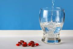 Pillole rosse con il vetro di acqua Fotografie Stock