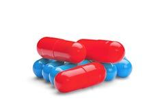 Pillole rosse e blu della medicina su fondo bianco isolato Fotografia Stock
