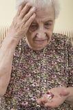 Pillole senior malate della tenuta della donna sulla palma immagine stock libera da diritti