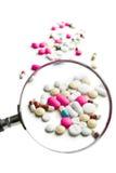 Pillole sotto la lente d'ingrandimento Fotografie Stock Libere da Diritti