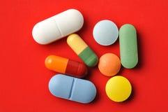 Pillole su colore rosso Fotografia Stock Libera da Diritti