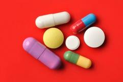 Pillole su colore rosso Immagine Stock Libera da Diritti