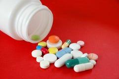 Pillole su colore rosso Immagini Stock Libere da Diritti