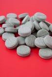 Pillole su colore rosso immagine stock