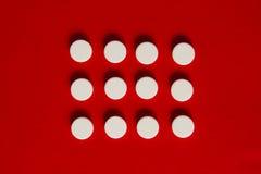 Pillole su un fondo rosso Immagini Stock Libere da Diritti